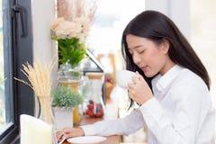 美丽的年轻亚裔妇女饮用的咖啡和微笑在咖啡馆、女孩坐在咖啡店的早餐和leisur的早晨 免版税图库摄影