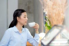 美丽的年轻亚裔妇女饮用的咖啡和微笑在咖啡馆,坐在咖啡店的女孩的早晨 库存图片