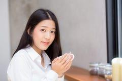 美丽的年轻亚裔妇女饮用的咖啡和微笑在咖啡馆,坐在咖啡店的女孩的早晨 免版税库存图片