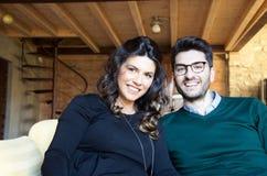 美丽的年轻人微笑的怀孕的夫妇坐沙发 免版税库存图片