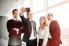 美丽的年轻商人做着selfie使用一个巧妙的电话并且在办公室屋子里微笑着 库存图片