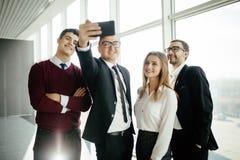 美丽的年轻商人做着selfie使用一个巧妙的电话并且在办公室屋子里微笑着 图库摄影
