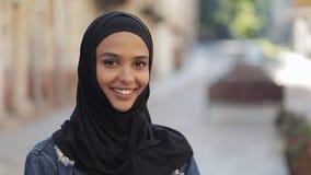 美丽的年轻回教微笑入在老城市的照相机身分的妇女佩带的hijab头巾画象  股票视频