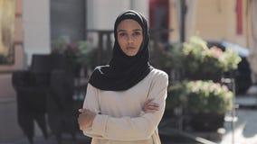 美丽的年轻回教调查照相机身分的妇女佩带的hijab头巾画象用横渡的手  影视素材