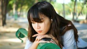 美丽的年轻在耳机的行家哀伤的亚洲妇女情感地听的音乐有智能手机的,坐公园长椅 影视素材