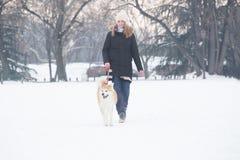 美丽的年轻女人和她的狗走在雪的公园的秋田 库存图片