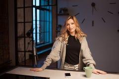 美丽的年轻女人在厨房里,清早,黑暗在公寓 图库摄影