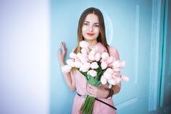 美丽的年轻女人在桃红色礼服藏品在手上反弹郁金香在蓝色墙壁背景的花花束 库存照片