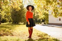 美丽的年轻女人在黑帽会议的秋天公园 图库摄影