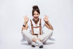 美丽的年轻女人坐地板,微笑的正面,做好标志用手和手指 成功的表达式 库存图片