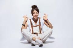 美丽的年轻女人坐地板,微笑的正面,做好标志用手和手指 成功的表达式 库存照片