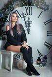 美丽的年轻女人坐大时钟圣诞节装饰的背景,拿着手电,等待假日 免版税库存图片
