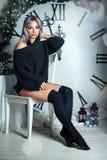 美丽的年轻女人坐大时钟圣诞节装饰的背景,拿着手电,等待假日 免版税图库摄影