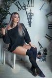 美丽的年轻女人坐大时钟圣诞节装饰的背景,拿着手电,等待假日 库存照片