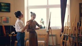 美丽的年轻女人学生和专业艺术家在车间,老师一起绘分享经验 影视素材