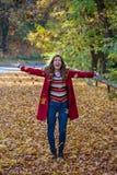 美丽的年轻女人投掷的秋叶在天空中,当sm时 免版税库存照片