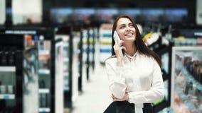 美丽的年轻女人画象谈话在电话在化妆商店 股票视频