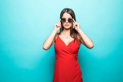 美丽的年轻女人的画象红色礼服的在蓝色背景 免版税库存照片