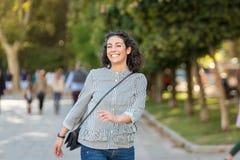 美丽的年轻女人获得乐趣在公园 免版税库存照片