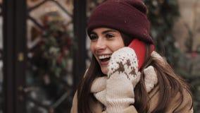 美丽的年轻女人谈话在电话,当她在街道上站立在商店窗口附近时 她笑 花雪时间冬天 股票视频