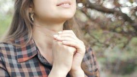 美丽的年轻女人转向上帝以在祷告的感觉,女孩交叉她的双臂在她的胸口和与谢意神色在