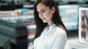 美丽的年轻女人选择在化妆用品的染睫毛油购物,比较品牌 股票录像