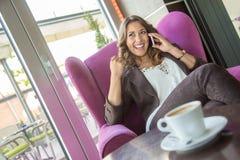 美丽的年轻女商人谈话在电话在咖啡馆 图库摄影