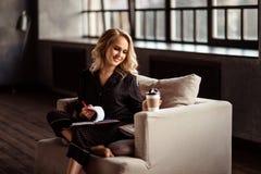 美丽的年轻女学生在笔记薄为即将来临的检查做准备及早在早晨,写笔记,享用热的咖啡 免版税库存图片