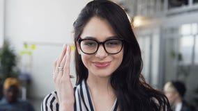 美丽的年轻女实业家固定的头发和微笑在与工作组的照相机的年轻商人 股票视频