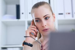 美丽的年轻女实业家讲的电话,当使用膝上型计算机和做一些文书工作时 库存照片