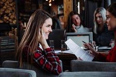 美丽的年轻女实业家谈话在咖啡馆和微笑的电话 免版税库存照片