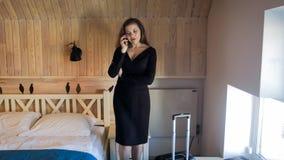 美丽的年轻女实业家走在旅馆客房和谈话由电话 免版税库存照片