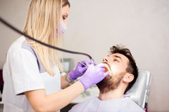 美丽的年轻女性一名年轻男性患者的牙医擦亮的牙牙齿诊所的 免版税库存图片