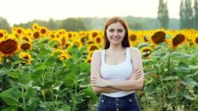 美丽的年轻女性农夫在一个领域的背景看照相机并且微笑着用向日葵 股票视频