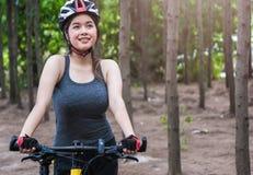 美丽的年轻女性妇女盔甲活动自行车 库存照片