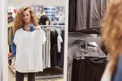 美丽的年轻女性射击在镜子看,去试穿白色T恤杉,立场在寄物处,做在衣物sto的购物 库存图片