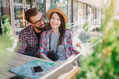 美丽的年轻女性游人坐与她的男朋友的长凳 她在照相机看并且微笑 他坐非常接近和 免版税图库摄影
