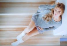 美丽的年轻孕妇坐一架木梯子的步 库存图片