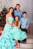 美丽的年轻家庭、父母和一个男孩有女孩的在演播室站立有圣诞树的背景 免版税库存照片