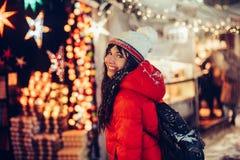 美丽的年轻微笑的妇女享受雪在圣诞节市场的冬时在夜城市佩带的帽子和红色夹克 免版税图库摄影