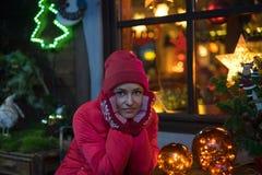 美丽的年轻微笑的妇女画象红色帽子的有defocused圣诞灯的在背景中 免版税库存照片