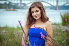 美丽的年轻微笑的深色的妇女画象草甸的在河附近 免版税图库摄影