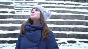 美丽的年轻微笑的白种人妇女特写镜头画象冬天夹克、帽子和围巾的 深色的女孩多雪的木头 股票录像