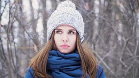 美丽的年轻微笑的白种人妇女特写镜头画象冬天夹克、帽子和围巾的 深色的女孩多雪的木头 股票视频