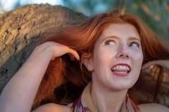 美丽的年轻性感的红发女孩对一根美丽的红色头发愉快地微笑着 库存照片