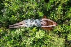 美丽的年轻性感的红发妇女,在绿色草甸放松的说谎,享用草本质上在新鲜空气的 喜悦 自由 免版税库存照片