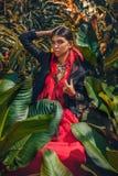 美丽的年轻时髦的女人与组成和摆在时髦的boho的辅助部件在自然热带背景 库存图片