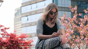 美丽的年轻欧洲女孩特写镜头坐街道和使用有摩天大楼的太阳镜的智能手机 股票录像