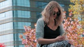美丽的年轻欧洲女孩特写镜头坐街道和使用有摩天大楼的太阳镜的智能手机 影视素材