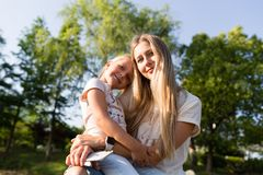 美丽的年轻母亲和女儿有金发拥抱的室外 做走的时髦的女孩在公园 o 免版税图库摄影